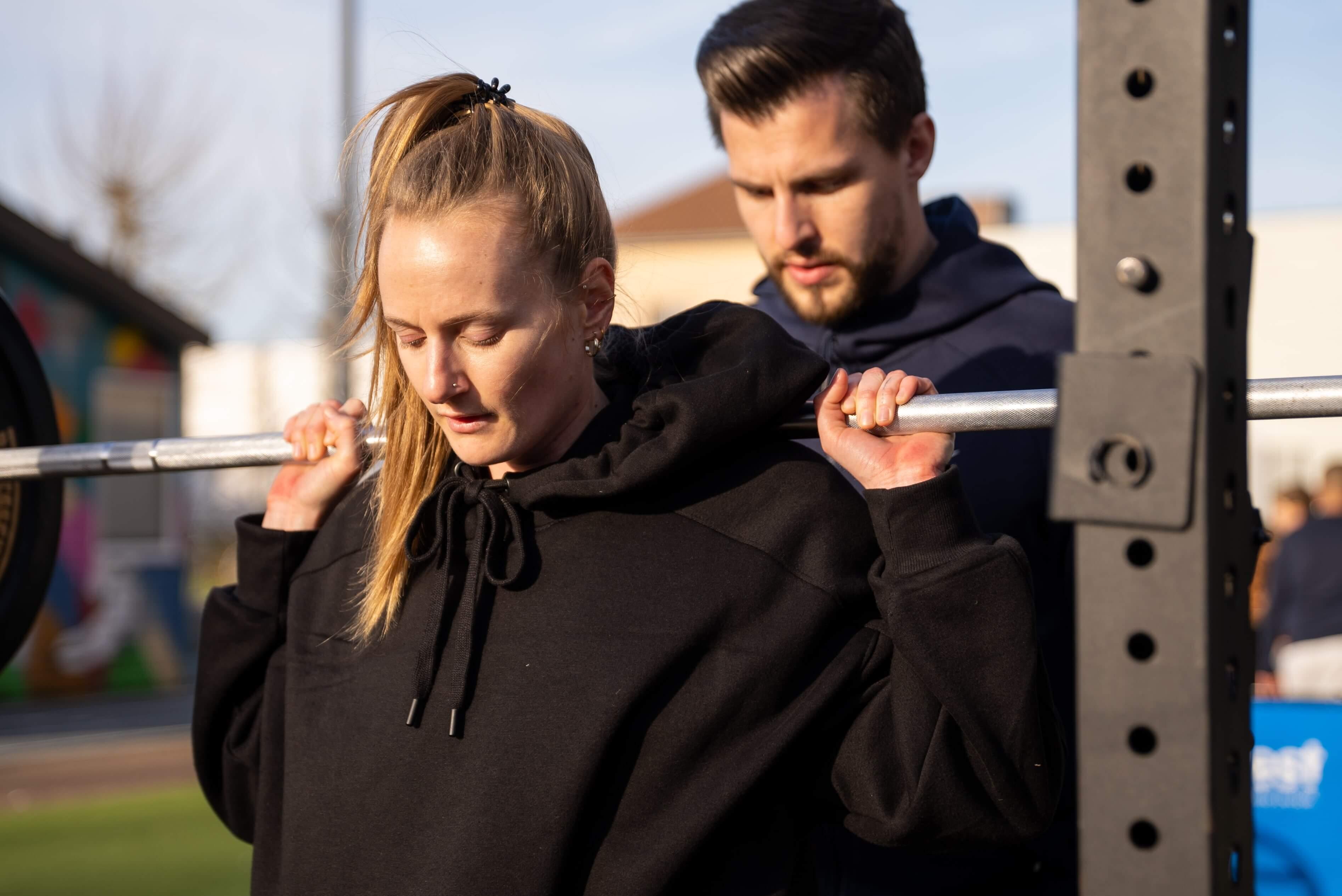 Jules helpt een vrouwelijke klant met squats