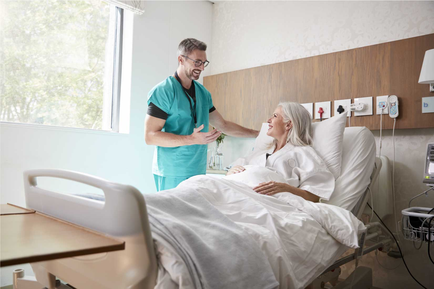 A surgeon in green scrubs standing smiling at the bedside of an elderly female patient