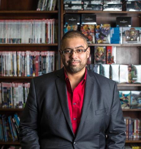 A portrait of Bilal Qizilbash surrounds by comic books and action figures.