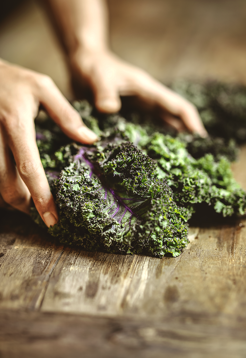Hands pulling apart raw leafy kale on a wooden cutting board.