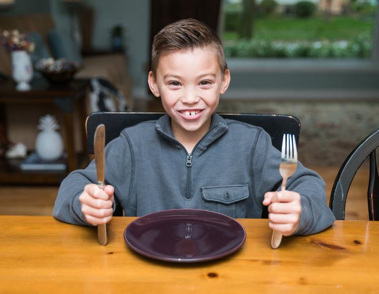 Smiling child sits at a kitchen table in front of an empty plate while holding a fork and knife.