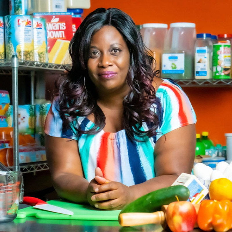 Regina Wallace posing in her element surrounded by baking tools and ingredients.