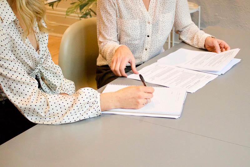Femme de face, derrière un bureau avec deux autres femmes vues de dos