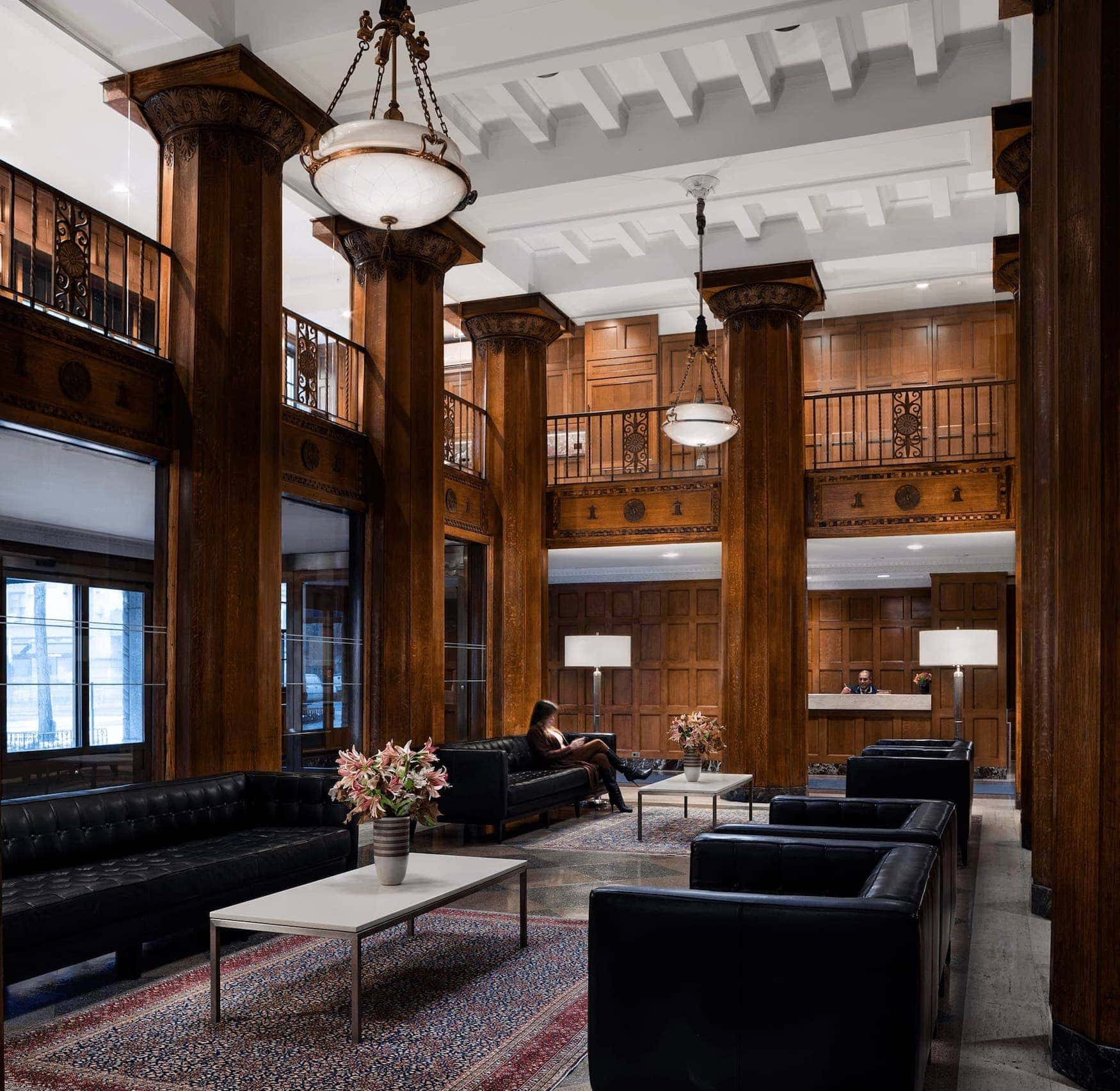 Fifth Avenue amenities with black seating, dark wood pillars, and white ceilings with exposed beams.