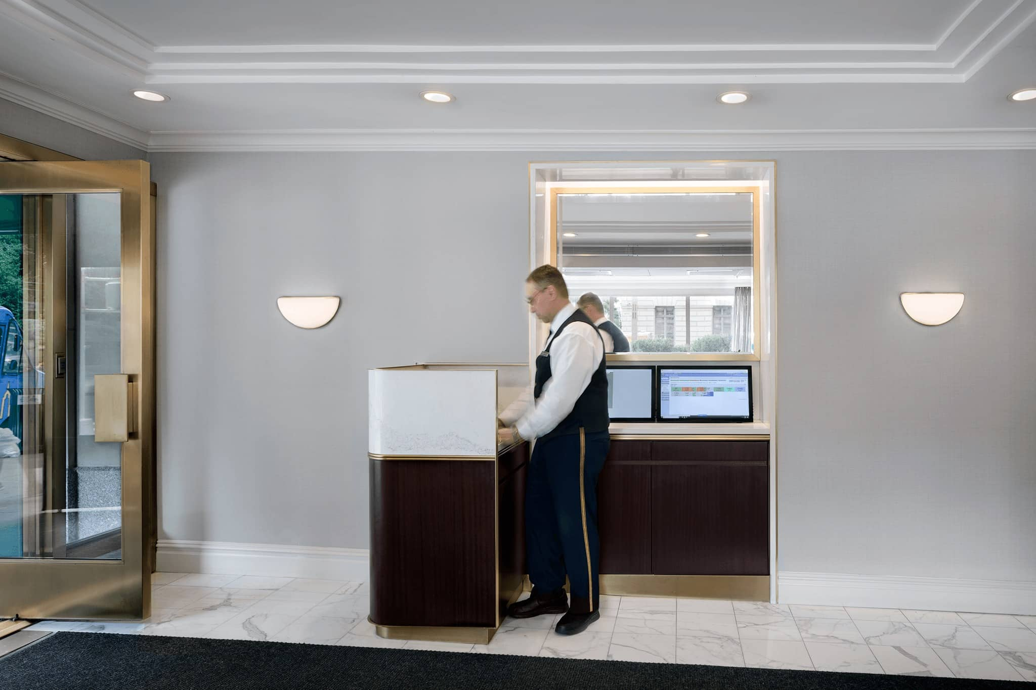 Man standing at concierge desk at 1050 Fifth Avenue.