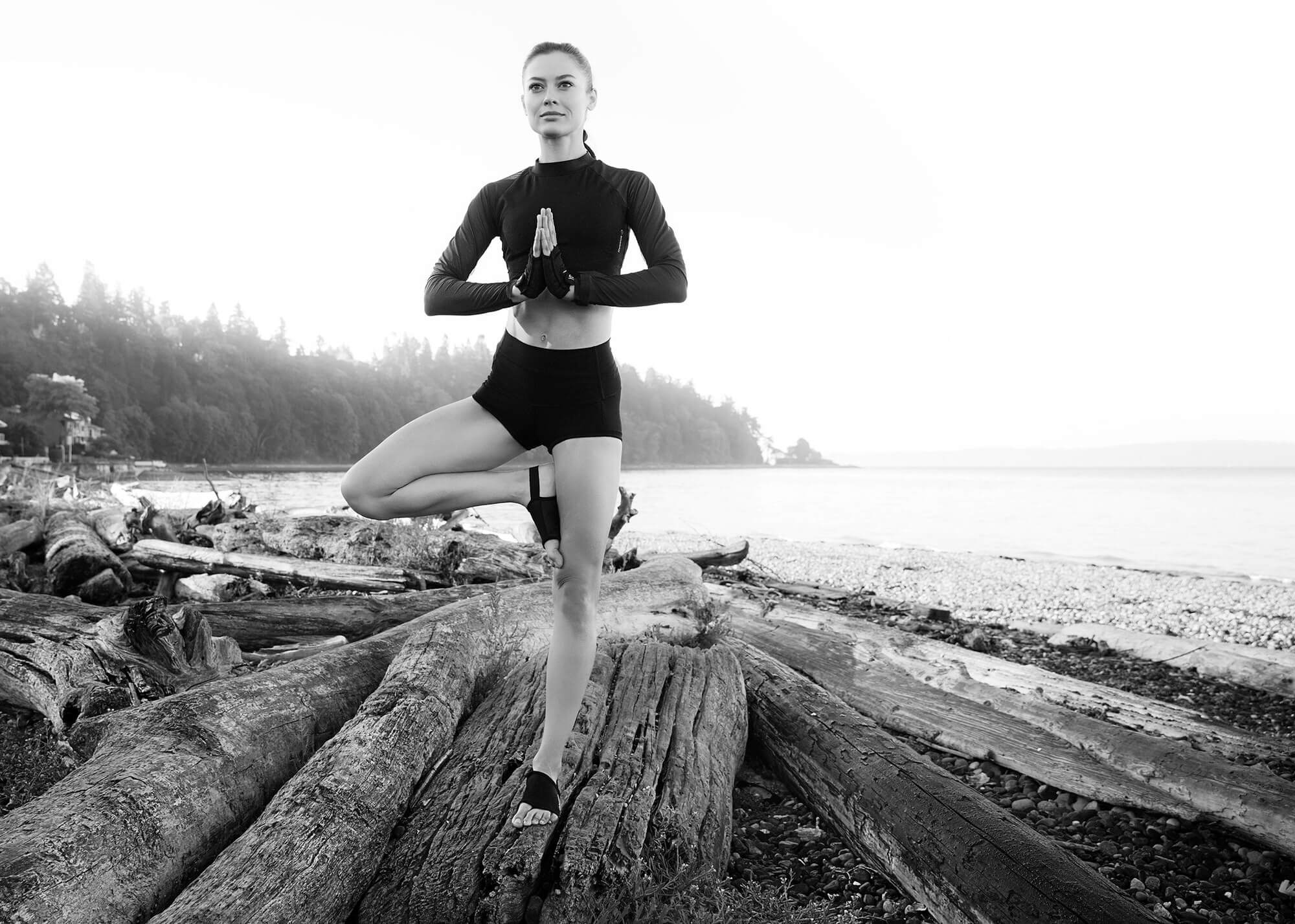 Fitness and yoga model balancing on beach