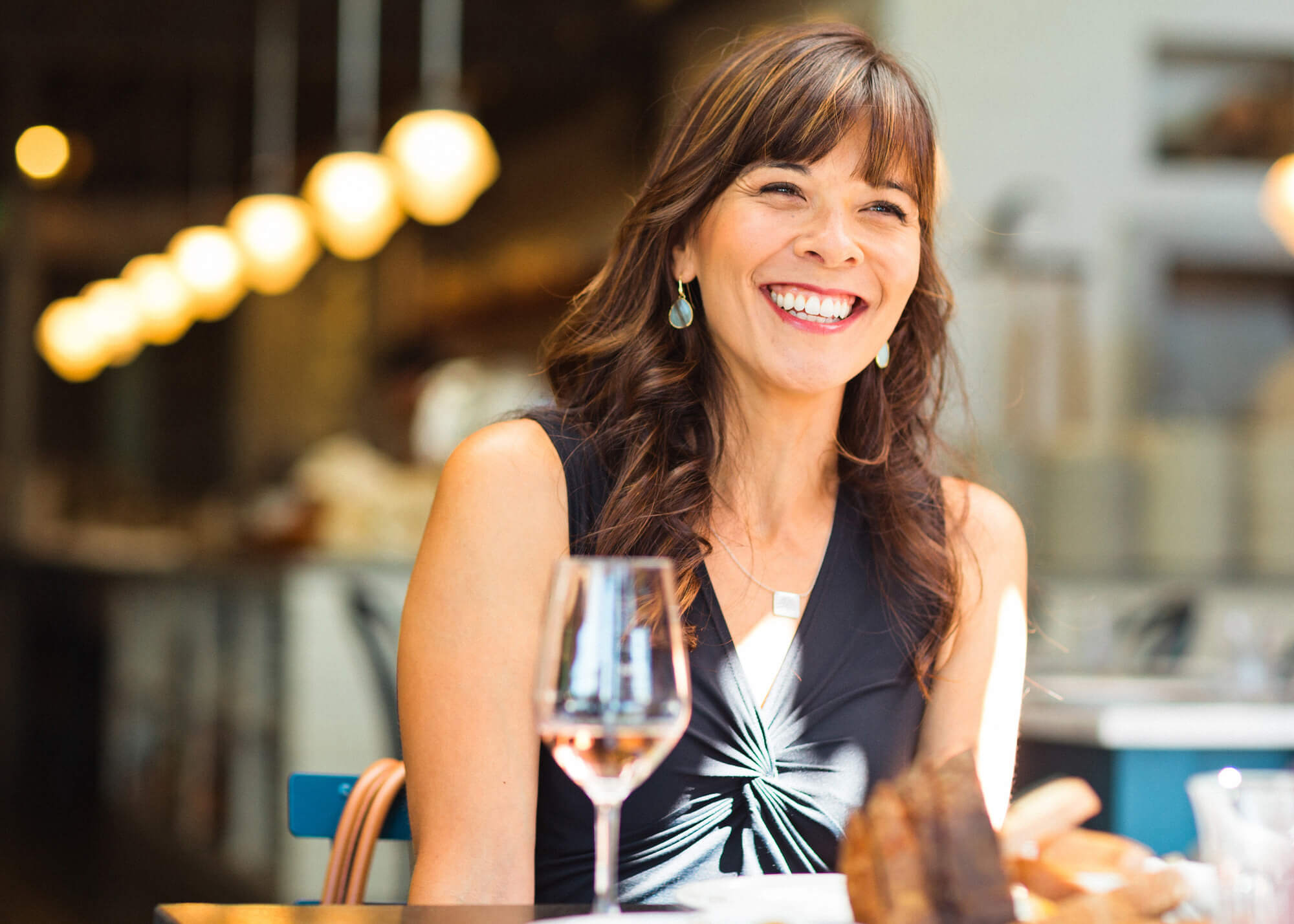 Woman with wine glass on restaurant patio