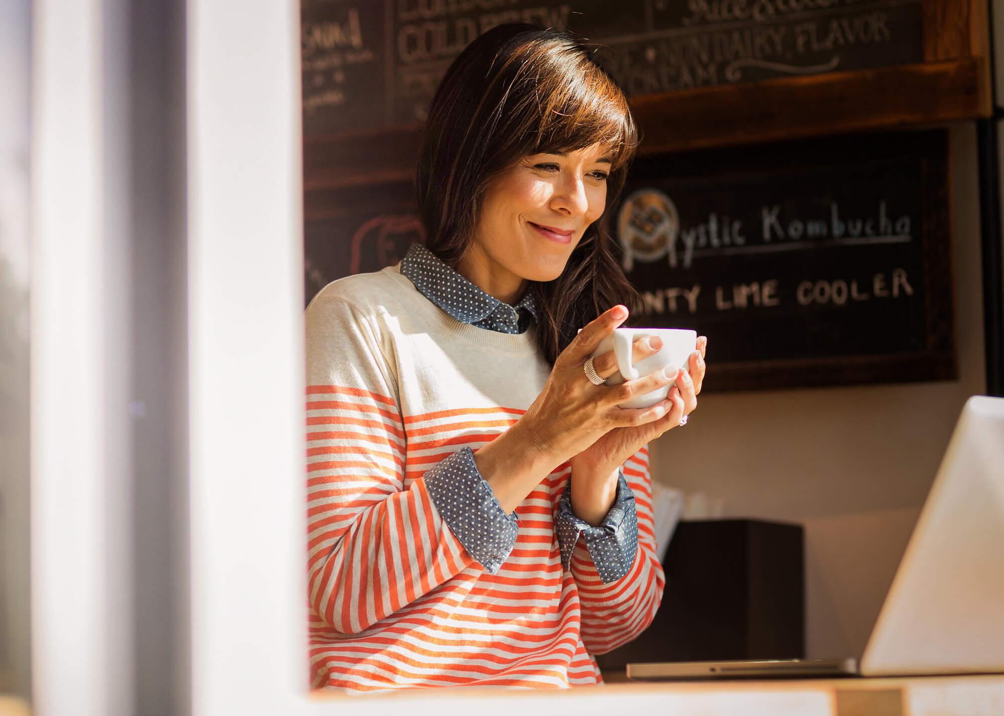 Woman at window ledge holding coffee