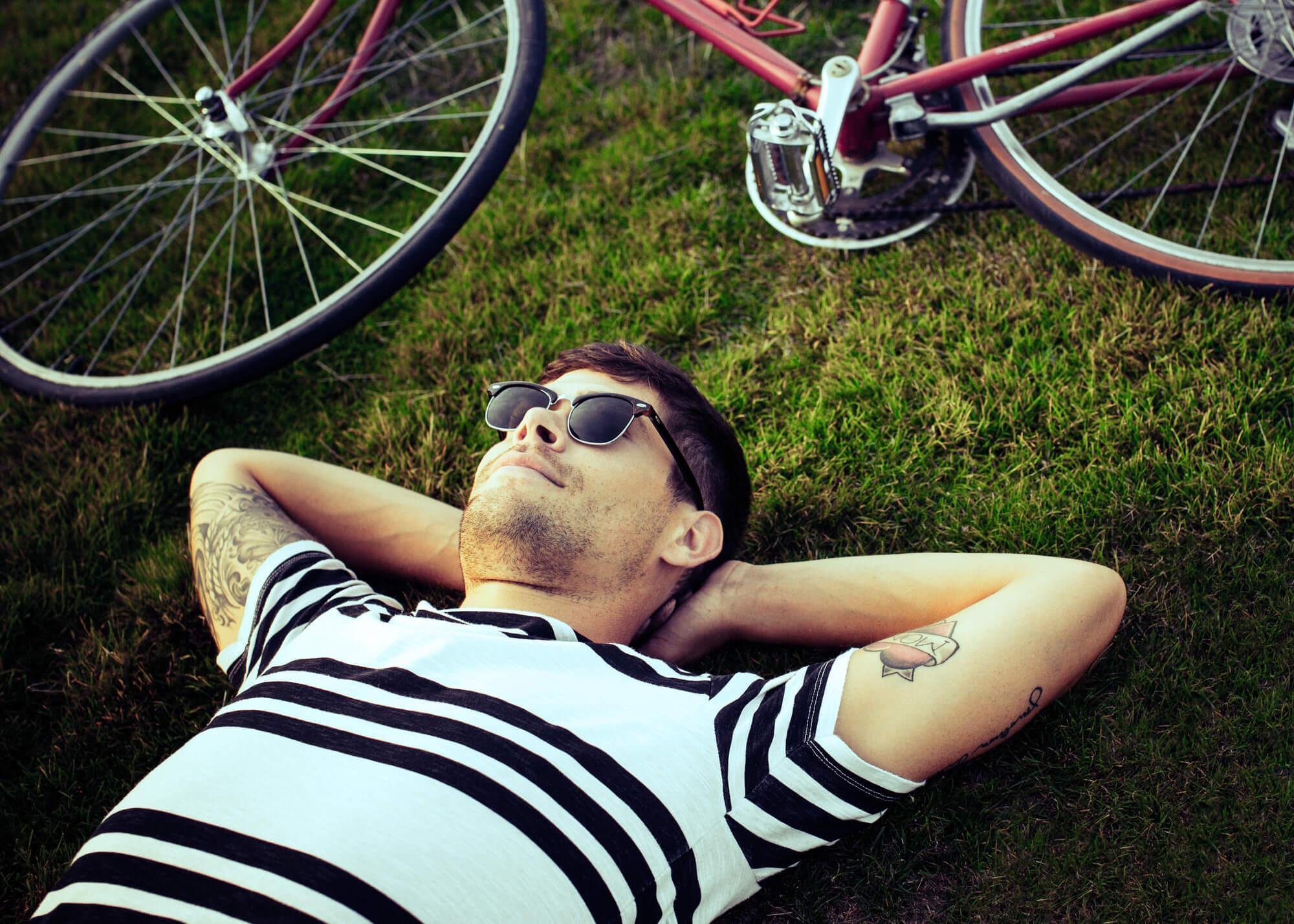 Man laying in grass with bike