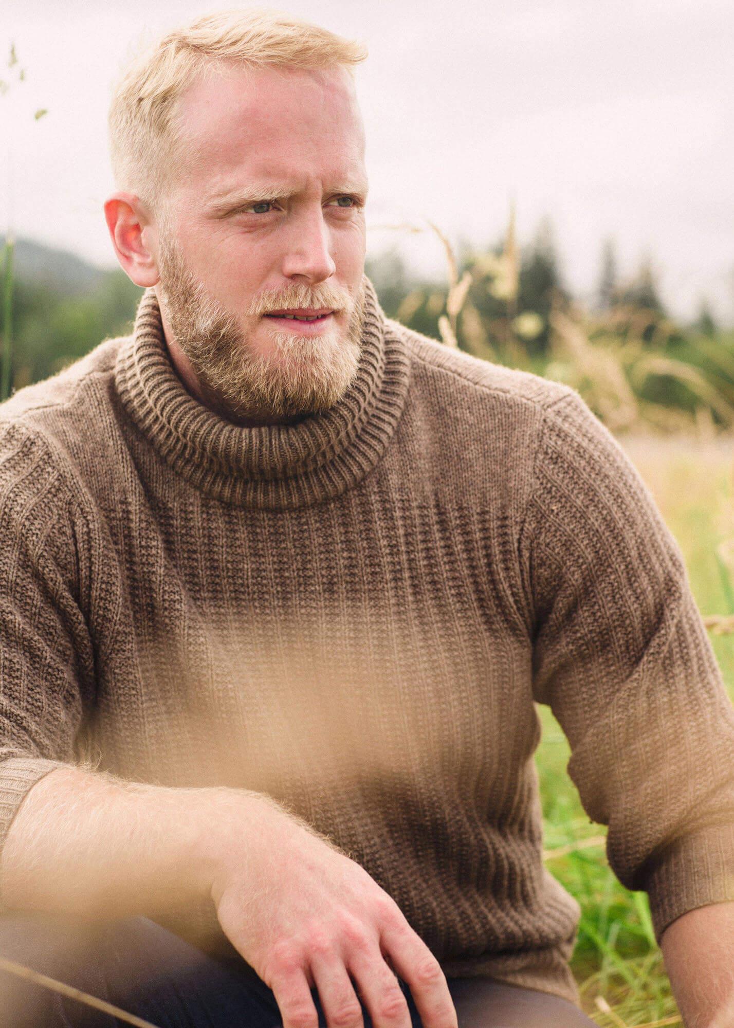 Man in sweater in grassy field