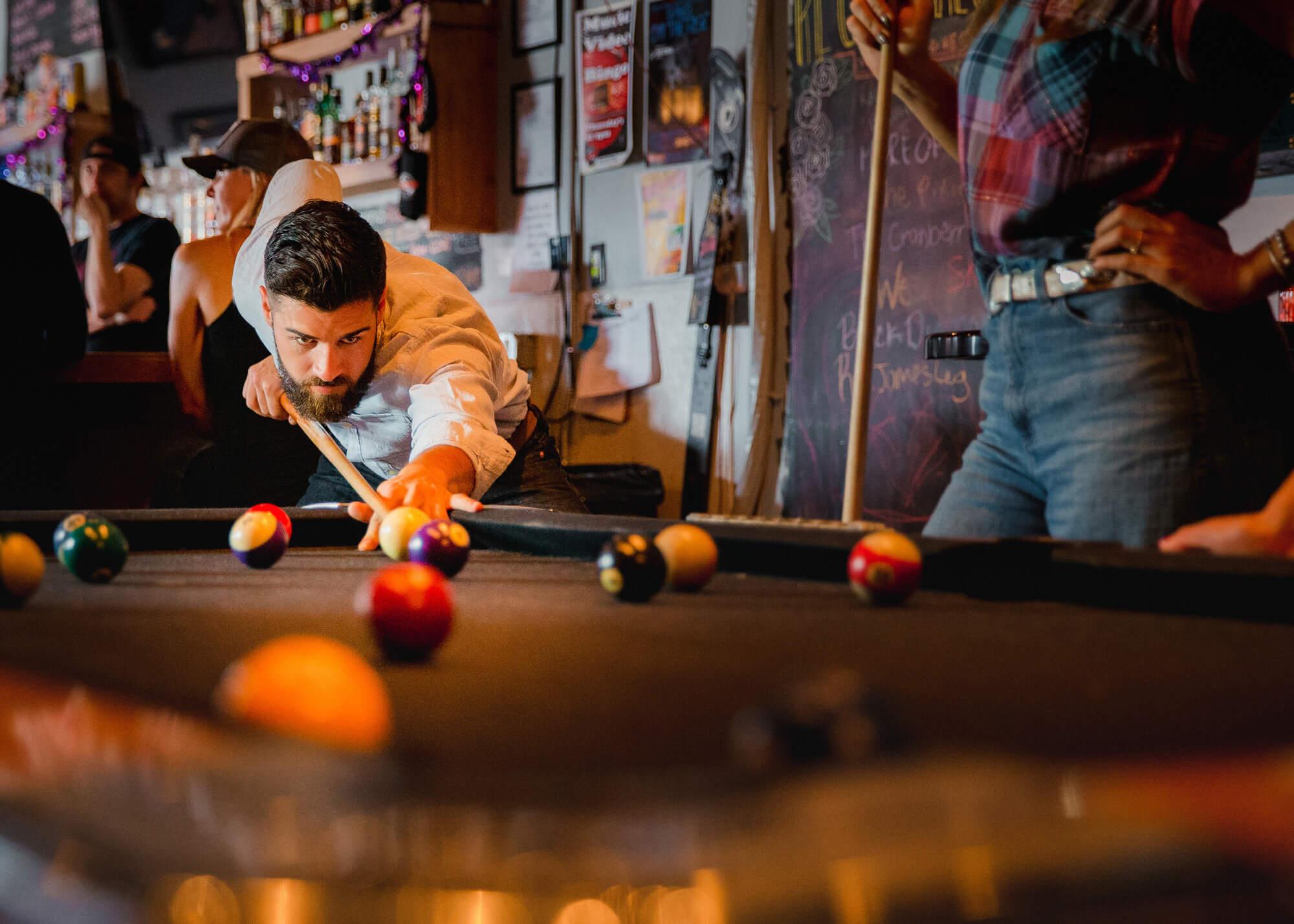 Man playing billiards in bar
