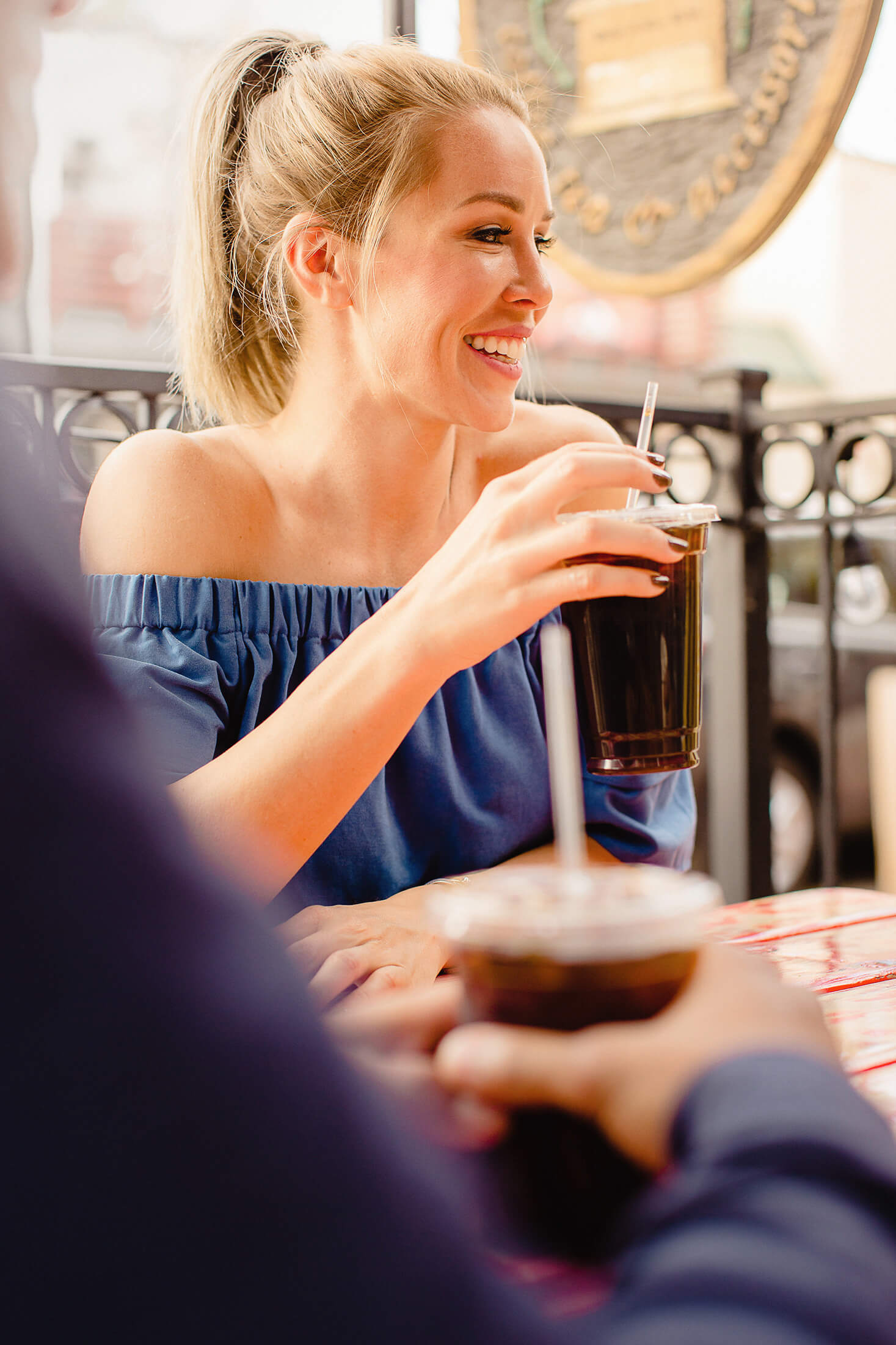 Woman drinking iced beverage on patio