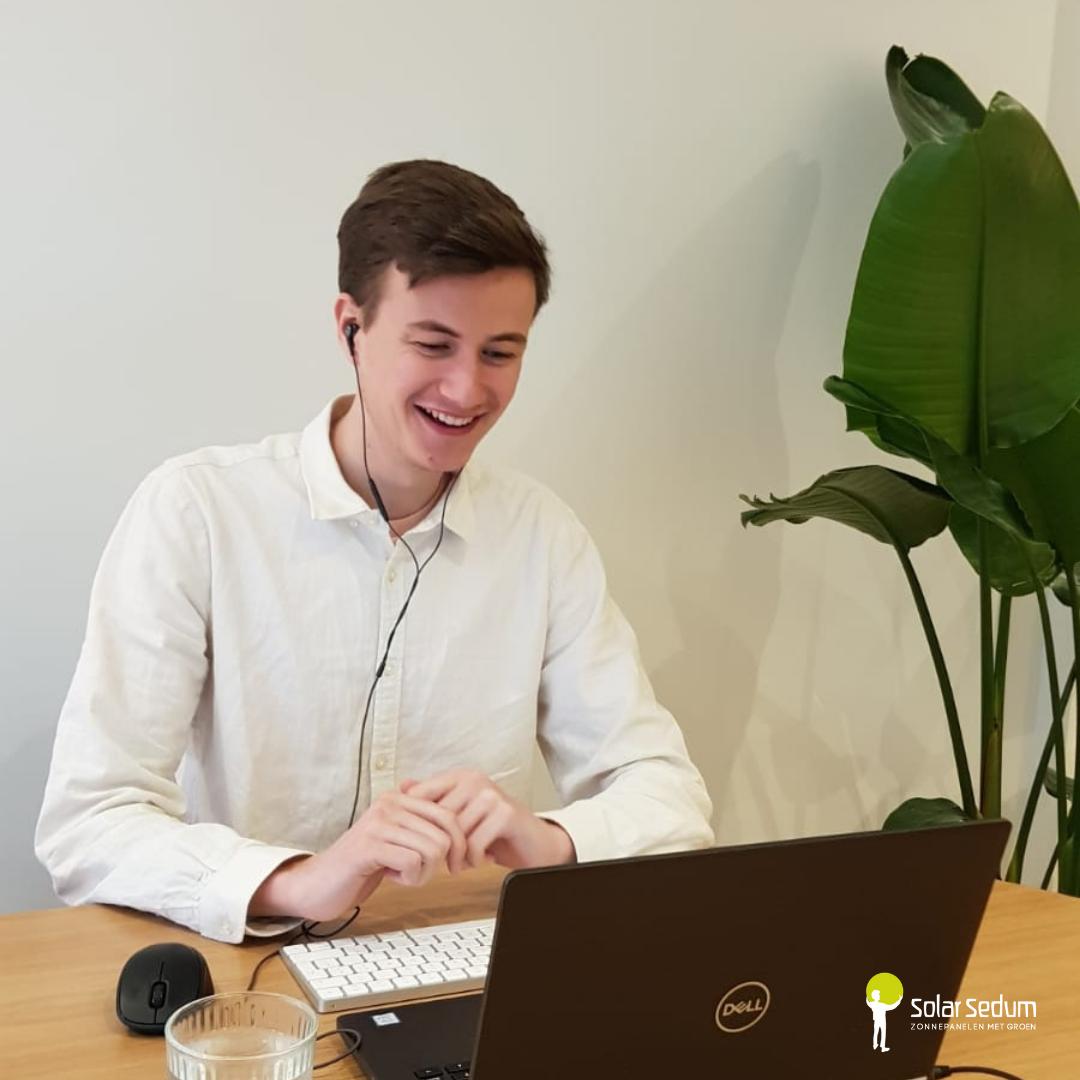 Een lachende medewerker van Solar Sedum in een wit overhemd met oortjes in achter een zwarte laptop