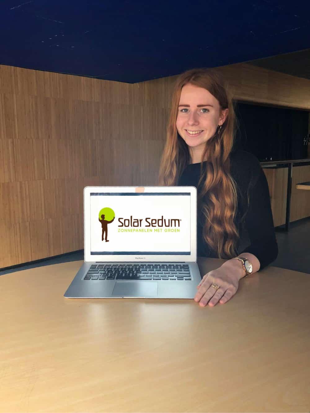 Een medewerker van Solar Sedum achter een latop met het logo van Solar Sedum er op