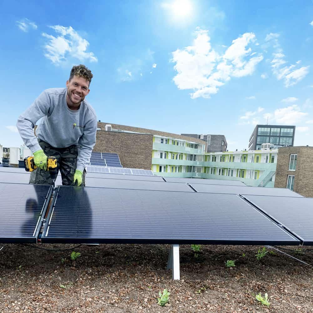 Medewerker van Solar Sedum op een dak die zonnepanelen installeert