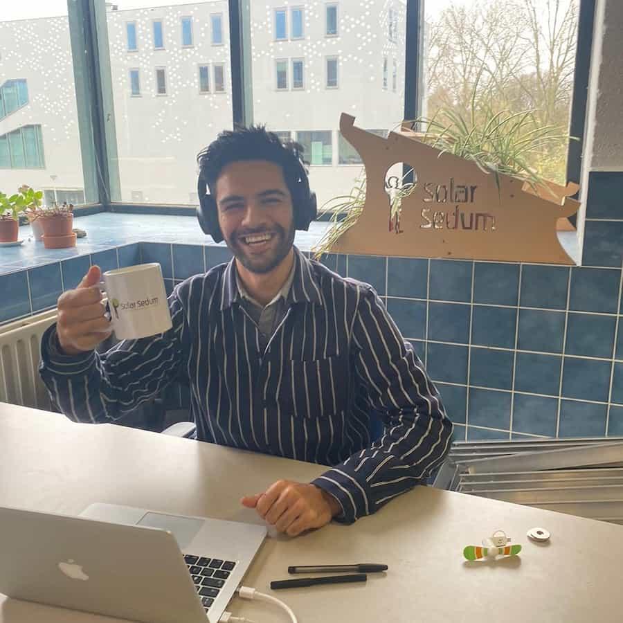 Lachende sales medewerker achter een laptop met een mok in de hand