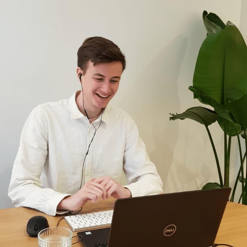 Medewerker van Solar Sedum achter een laptop met oortjes in en een plant ernaast