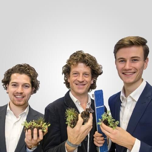 De 3 oprichters van Solar Sedum in pak met sedum plantjes en een miniatuurzonnepaneel in de handen