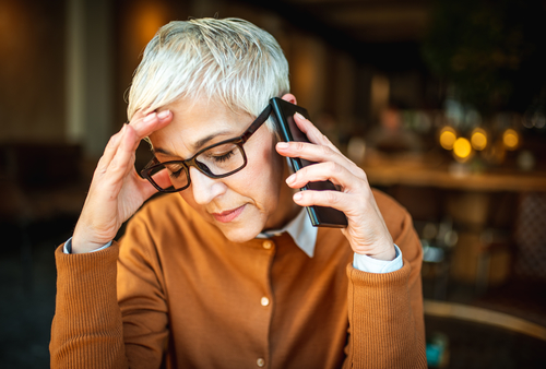 A older business woman, with short white hair, holds her hand up to her forehead as she takes a call. Her eyes are shut and she looks disappointed with the news she's receiving. Now, she's got to figure out how to reduce churn after this bad customer experience.