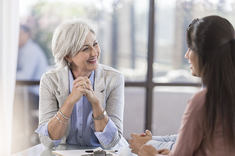 An older business woman with white hair leans forward as she listens intently to another younger woman as she explains something. Social listening is engagingly listening