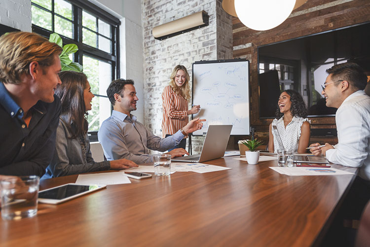 Content and social marketing strategist in a meeting discussing their audience and what patterns they have notices through Nuvi's Language Engine and social listening tools.