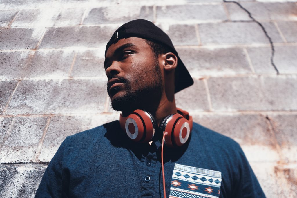 A black man wearing red, ear-covering headphones, looks toward his right. He stands in front of a gray brick wall. He is wearing a ball cap backwards. He, like many influencers, is showing off brands through fun and innovative ways.