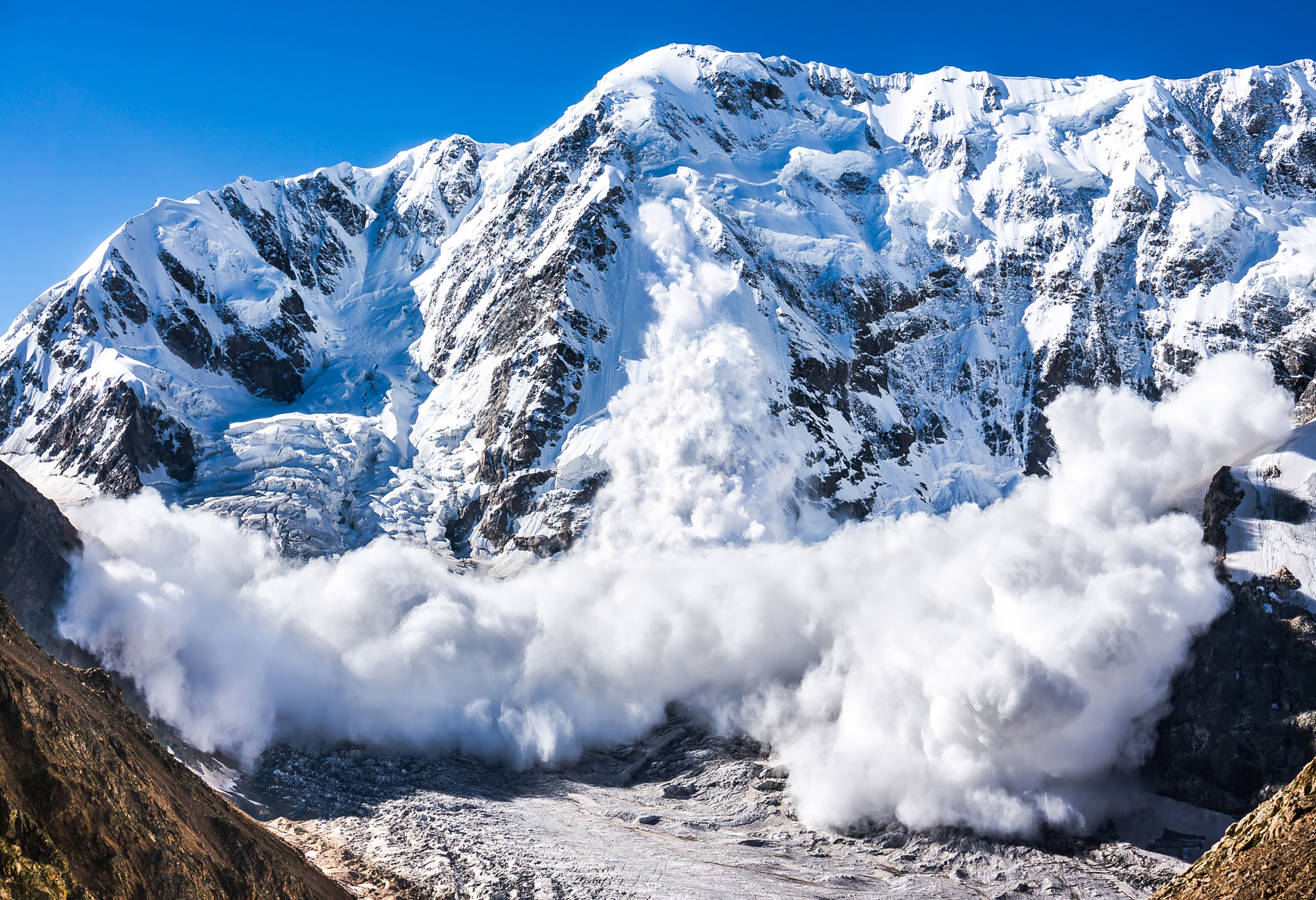 An avalanche of white snow descents from a central point on the mountain face in the center of the image. Avalanches can be controlled and prevented just like PR crises.