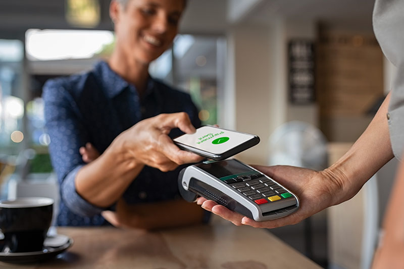 A customers holds their phone over a portable check out machine that an employee is holding up. The phone displays a green circle with a check mark in it. Beneath the circle are the words Payment Sent. An easy purchasing process can encourage customers to repurchase.