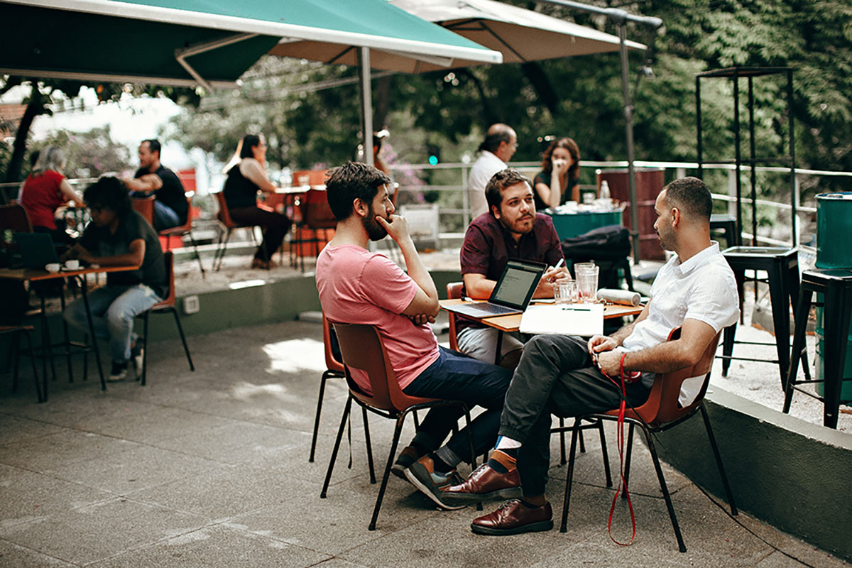 Three men in their late 20's to mid 30's sit together at a table outside. They enjoy their conversations together. Friends trust each other and companies need to try to develop that kind of relationship with the customers.