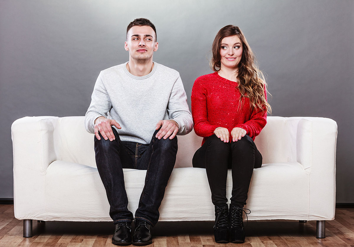 A young man and woman sit on a low backed white couch. They're stiff and not quite making eye contact. They're definitely feeling awkward. This, in many ways, could be the representation of companies and customers. They don't quite know how to interact besides traditional marketing and customer service interactions.