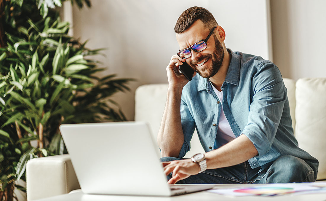 A white man with glasses and closely trimmed beard and hair cut smiles as he talks on the phone. He's sitting on his couch as he works from home. He looks at something on his computer screen as he talks. Let your remote workers relax and be able to do their work, knowing that their job is secure.