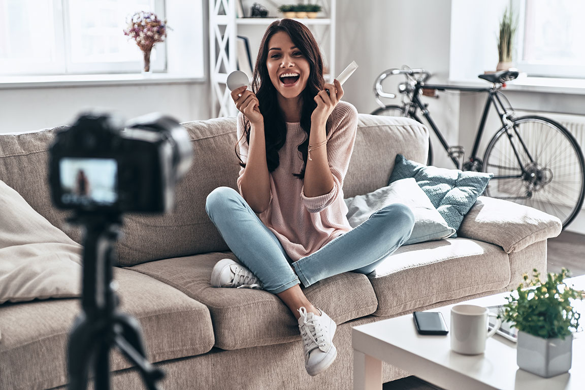A young woman with dark brown hair, wearing a pale pink sweater, sits on her couch facing a camera. She excitedly holds two long boxes in her hands next to her face. She seems to be talking animatedly to the camera. She's an influencer with makeup products.