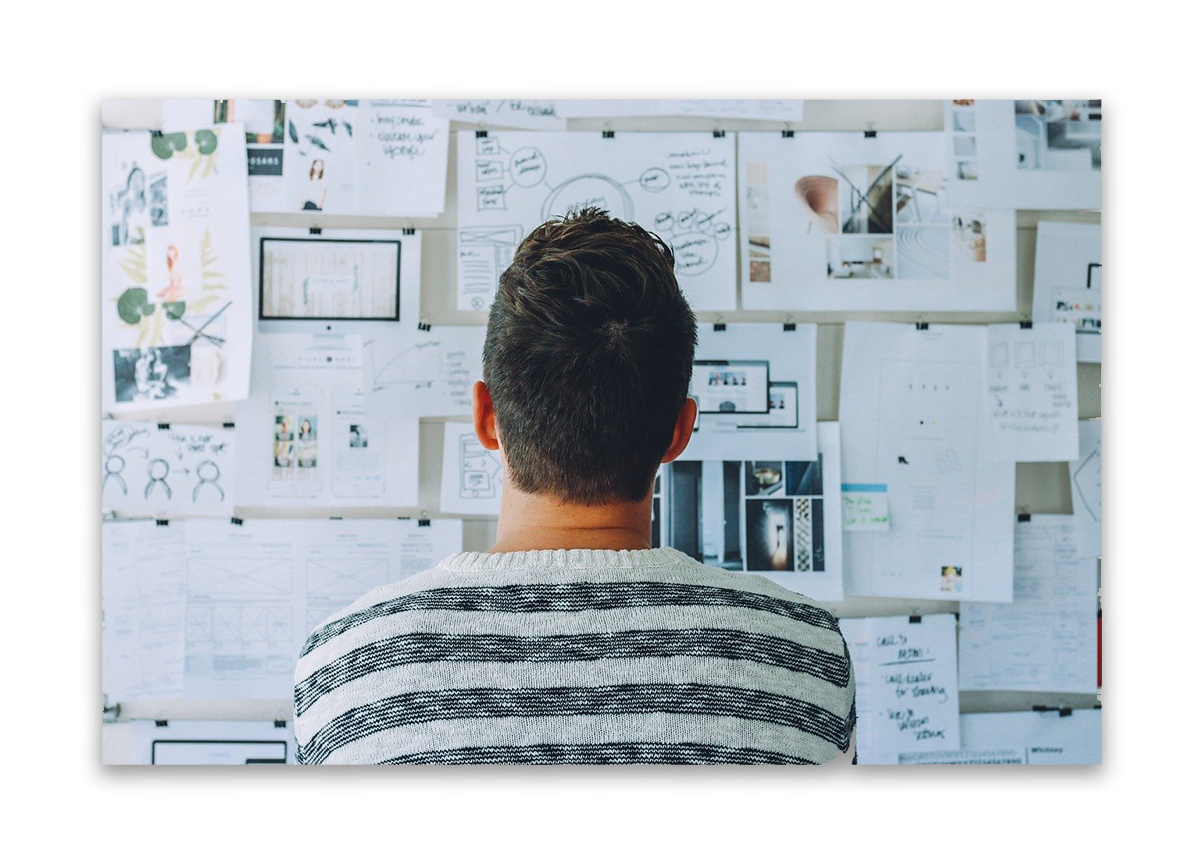 A young man with brown hair has his back to the camera. He is studying a board on which many pages have been push pinned to. They are a conglomeration of images that show the elements of the customer journey and market research.