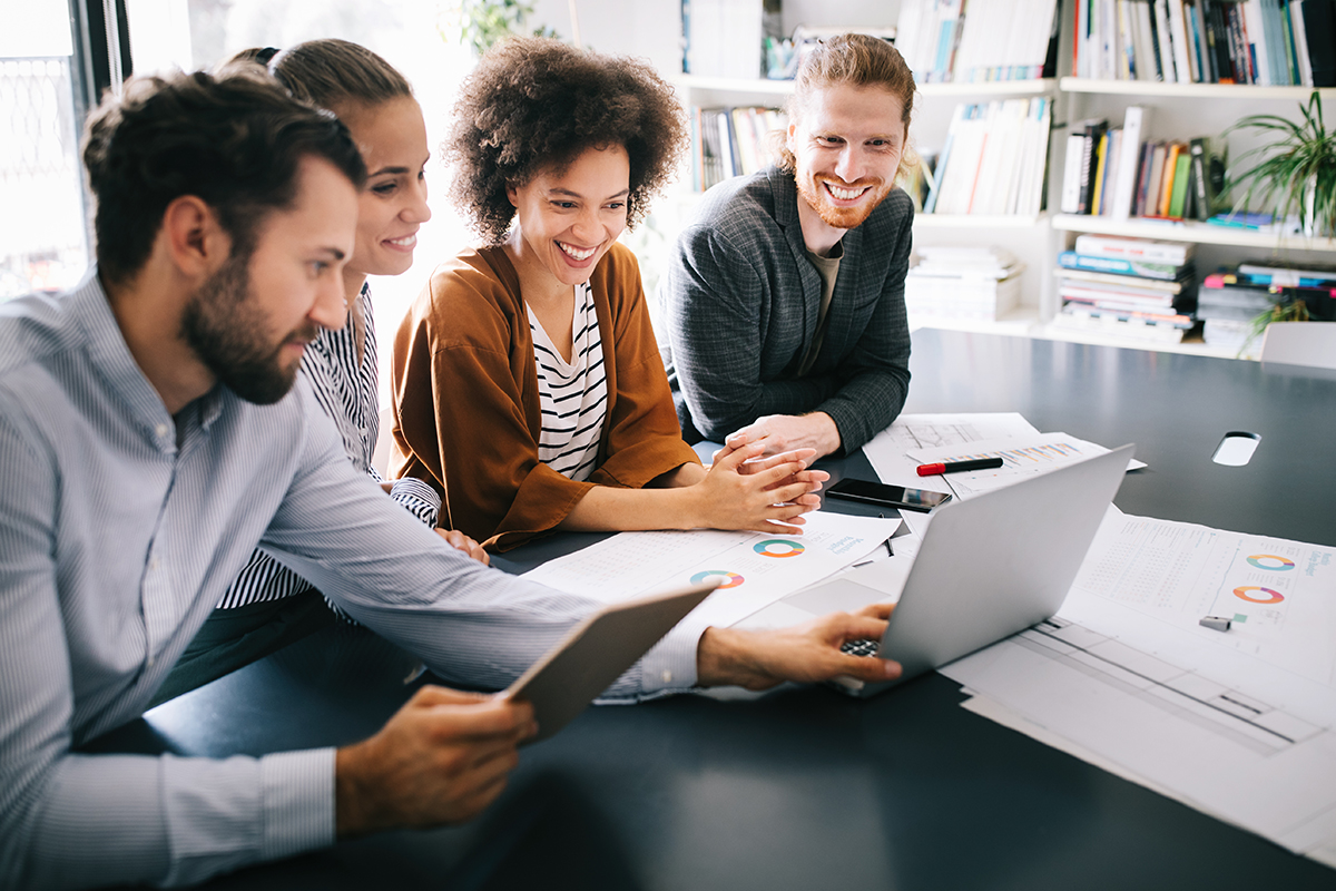 Four coworkers, two men and two women, are discussing what they see on a laptop screen. Around the laptop are several pages of market research data. The four coworkers are creating a social customer experience journey for their clients based on their market research data