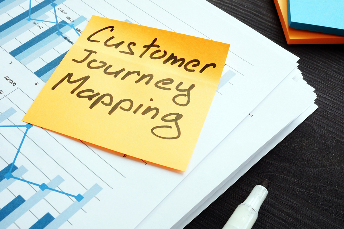 A yellow sticky note is attached to a document with many graphs that uses a monochromatically blue layout. The graphs are overlaid bar charts and line graphs. The yellow sticky note is it's top right corner sticking up off the page. Written on it with thick black sharpie is the words Customer Journey Mapping. This image hints at the strategic planning needed to create a customer journey focused on the experience of the customers