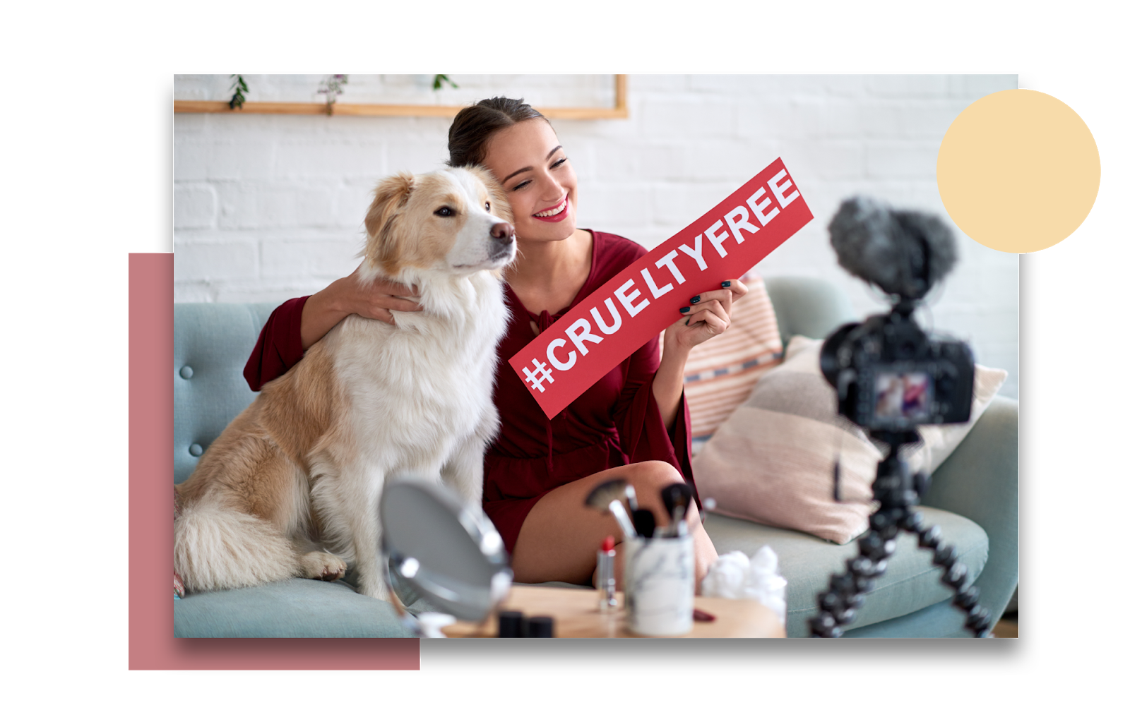 A young woman that is an influencer is recording herself during a make up tutorial or review. She is sitting on her couch with her dog beside her. As she smiles at the camera and cuddles up to the dog, she holds up a sign that says #crueltyfree