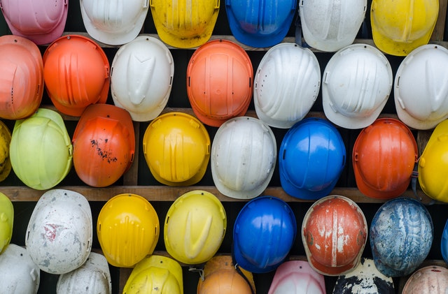 Different color and types of hard hats hanging up next to each other with various wear and usage.