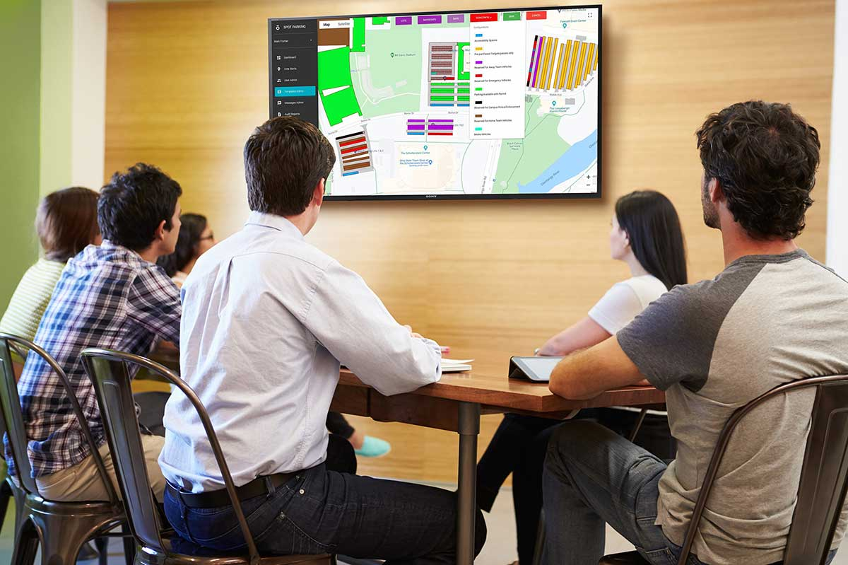 Event staff meeting reviewing Spot Campus admin panel on TV screen
