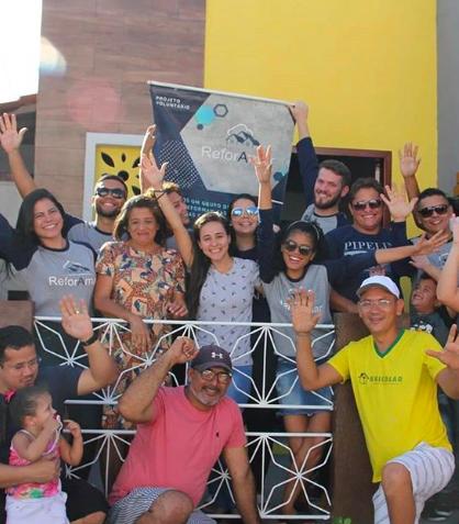 Membros do projeto ReforAmar em frente à uma casa reformada