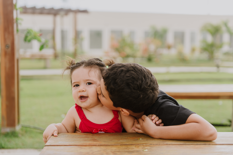 Irmão beijando a bochecha da irmã bebê