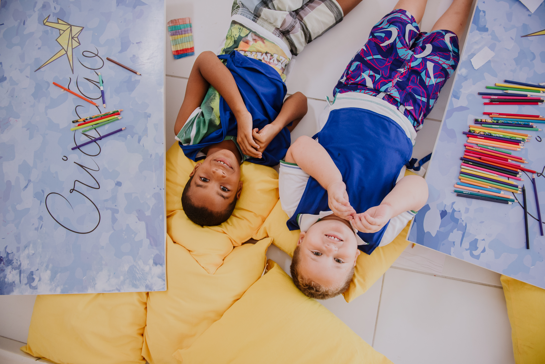 meninos sorrindo deitados em almofadas no Espaço Kids