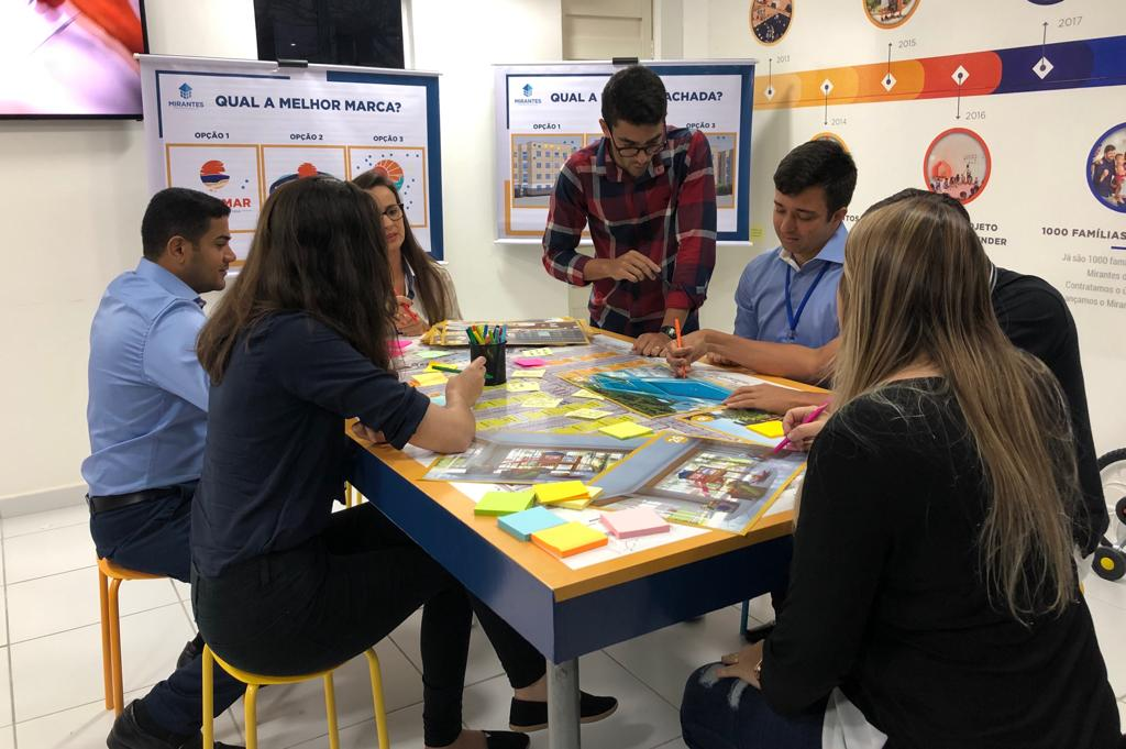 Pessoas em uma mesa com muitos objetos coloridos e compartilhando ideias