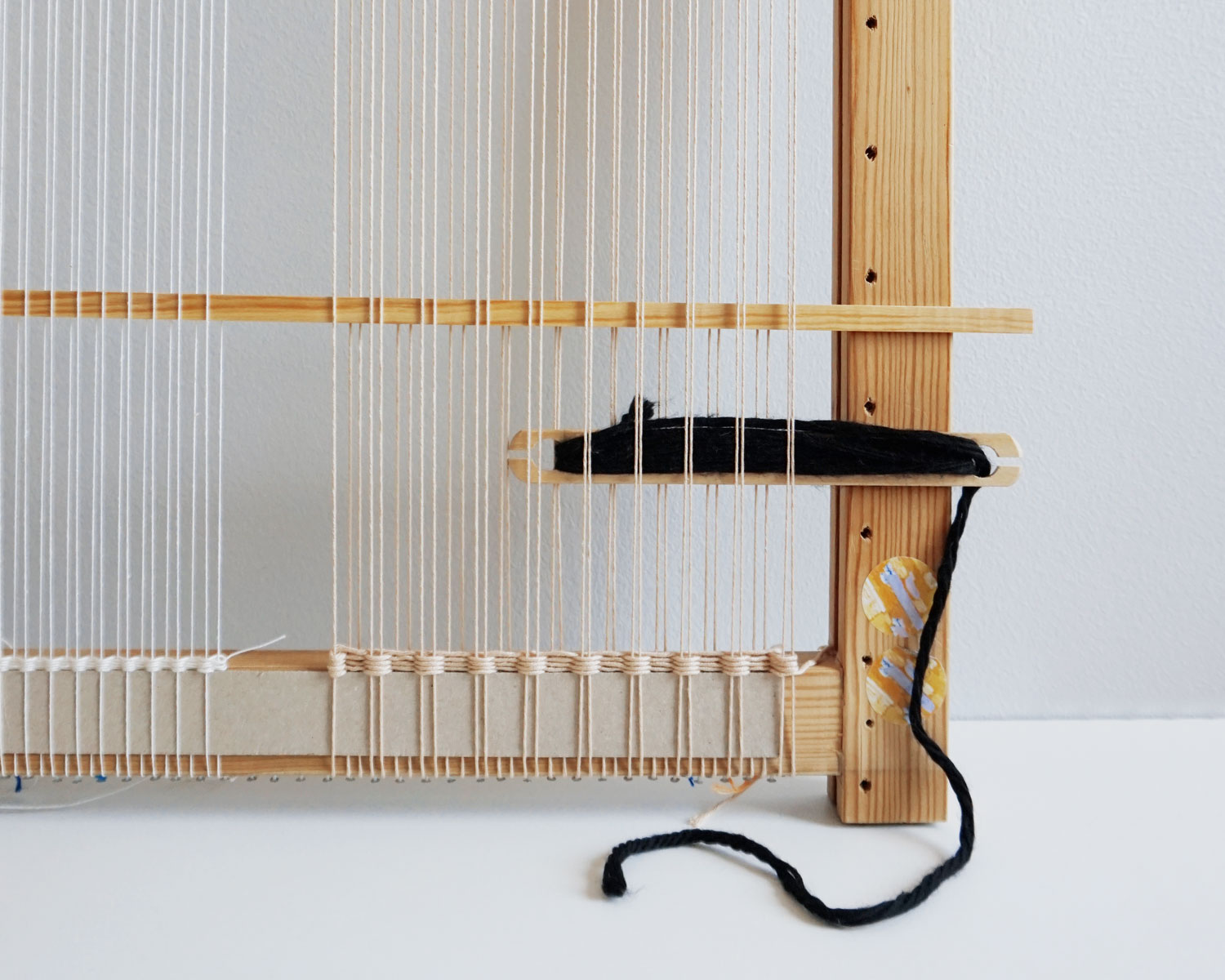 Image of a simple frame weaving loom with a weaving shuttle