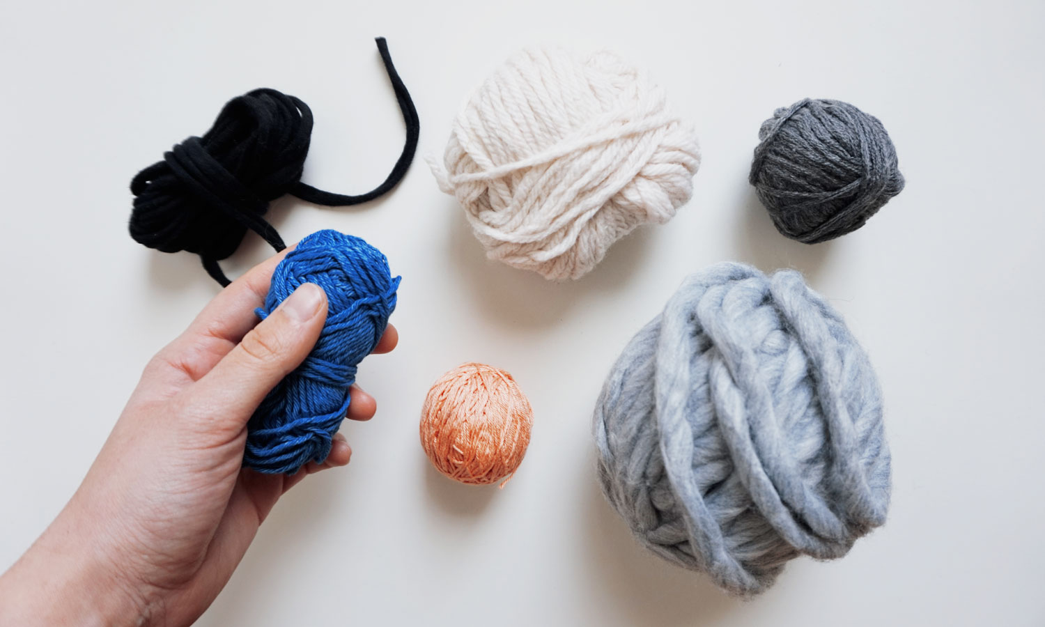 Image of 6 different color balls of yarn on a white brackground. A hand is holding one of them