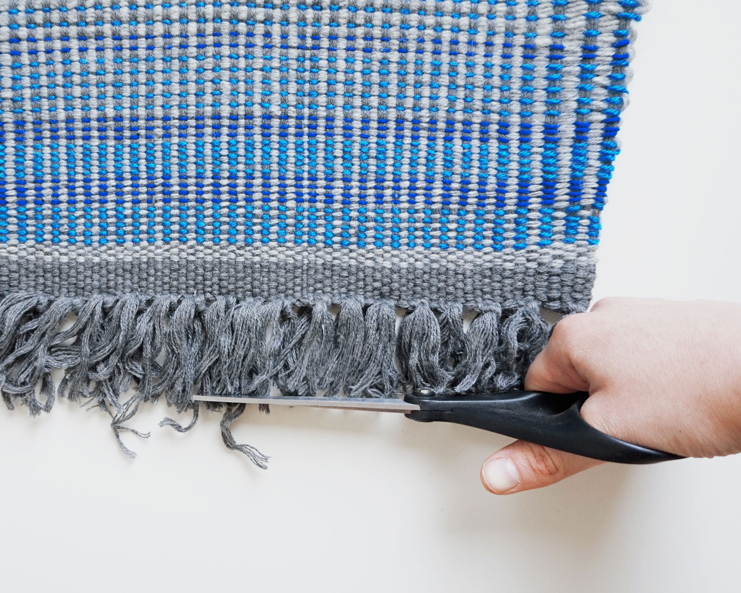 Image of a hand with scissors cutting the fringe of a woven piece of fabric
