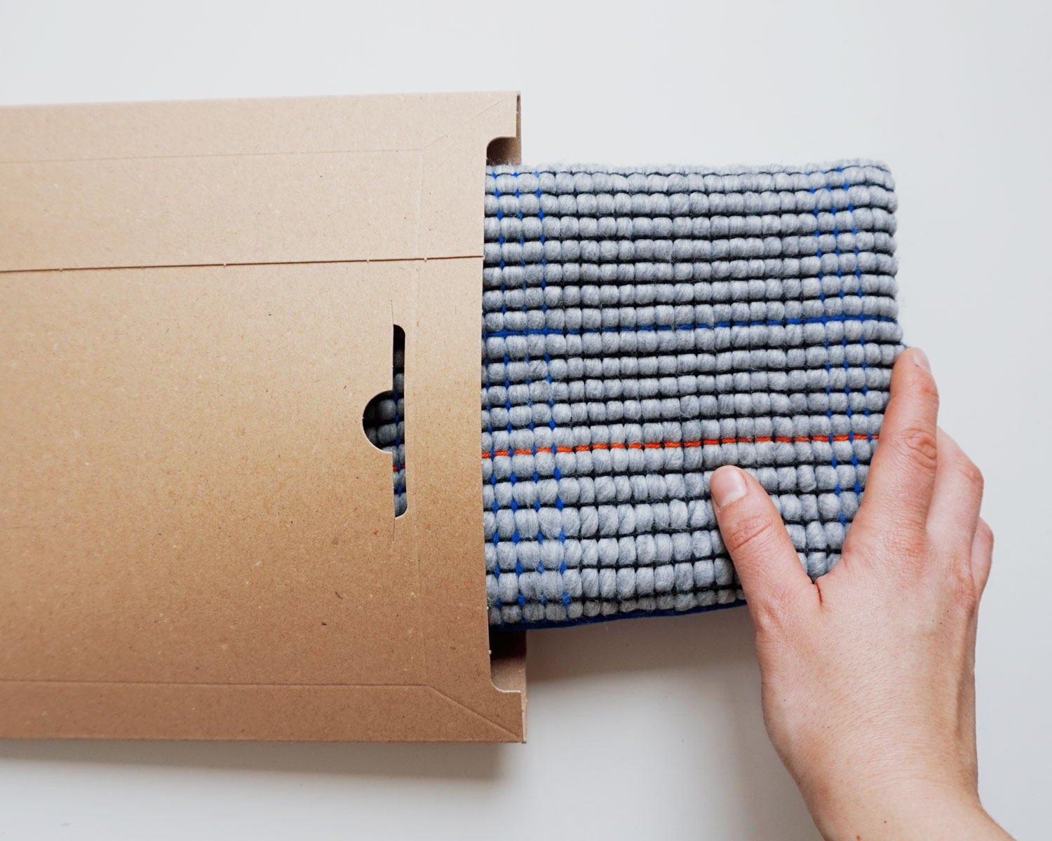 Image of a hand packing a pillow case into a cardboard envelope