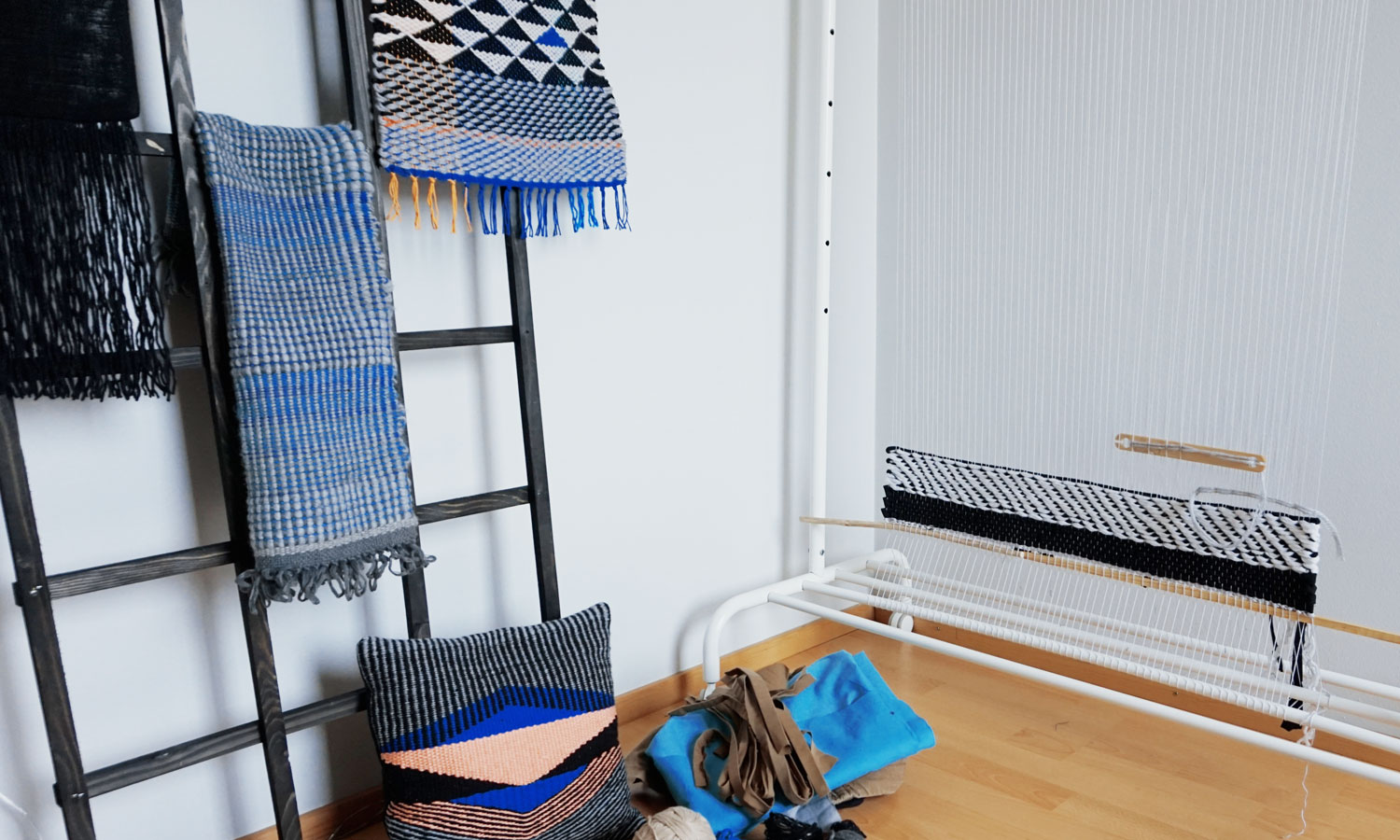 Image of a corner of a room with a large weaving loom and an assortment of textile home goods
