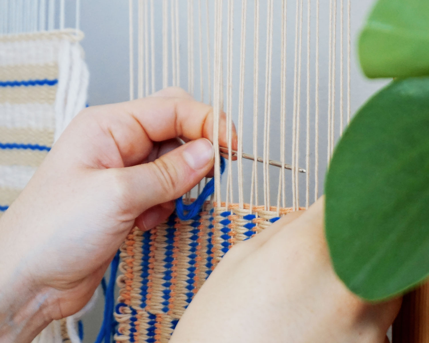 Close up of hands working on the weaving loom. Some leaves of a plant in the foreground