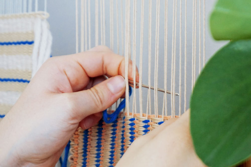Two hands working at a weaving.