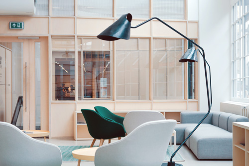 A sparce office interior with chairs, sofa and lampshades.